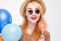 Portrait of hipster girl with lollipop and balloons. Portrait of fashionable smiling hipster girl with lollipop and balloons. Happy young woman in sunglasses and Stock Photography