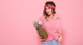 Portrait of hipster girl and pineapple isolated on pink background royalty free stock photography