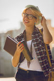 Portrait of hipster girl on street with notebook and cup of coff Royalty Free Stock Photo