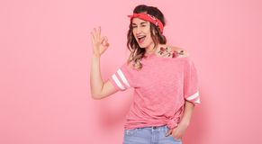 Portrait of a hipster girl with tattoo,  on pink background royalty free stock photo