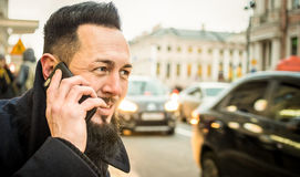 Portrait of hipster guy calling taxi in city center - Autumn fas Royalty Free Stock Image