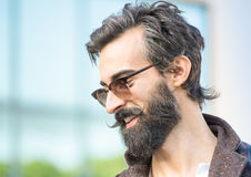Portrait of hipster guy with confident face expression - Autumn. Fashion male model posing outdoors - Young man with beard and alternative mustache Stock Photography