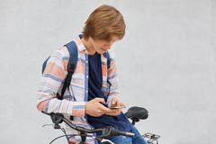Portrait of hipster guy with trendy hairstyle wearing shirt and jeans holding backpack standing near his bicycle using smart phone stock photos