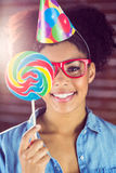 Portrait of a hipster hiding herself behind a lollipop Stock Images