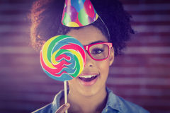 Portrait of a hipster hiding herself behind a lollipop Royalty Free Stock Photo