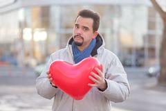 Portrait of a hipster man with a beard posing with a red air heart shape balloon in city street with tender face expression. Young bearded hipster man posing stock photos