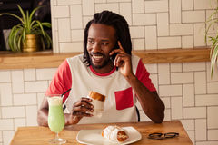 Portrait of hipster man on the phone while eating Royalty Free Stock Photos