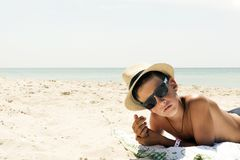 Portrait of hipster relaxing boy in hat and glasses on beach. Profile portrait of teenager boy in hat on beach Stock Images