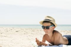 Portrait of hipster relaxing boy in hat and glasses on beach. Profile portrait of teenager boy in hat on beach Stock Photos