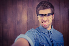 Portrait of hipster sticking out tongue. Against wooden wall Stock Images