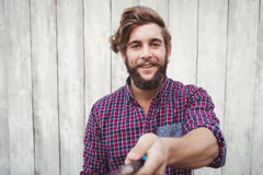 Portrait of hipster using selfie stick Stock Photography