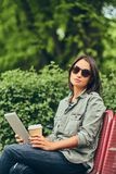 Hipster woman in a sunglasses with a coffee and tablet computer Royalty Free Stock Photo
