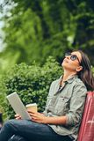 Hipster woman in a sunglasses with a coffee and tablet computer Royalty Free Stock Photos