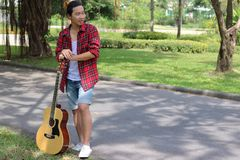 Portrait of hipster young man relaxing holding acoustic guitar at the park outdoors stock photography