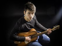 Young man or teenager playing guitar in studio. Portrait of hipster young man or teen playing guitar against black background, in studio shot Royalty Free Stock Photos