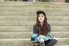 Portrait of hipster young woman with skateboard sitting on stair Royalty Free Stock Photos