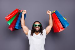 Portrait of his he cool trendy attractive cheerful cheery wavy-haired guy 3d eyeglasses eyewear holding in hands rising. Up colorful bags isolated over gray royalty free stock photo