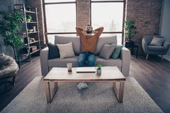 Portrait of his he nice attractive bearded guy sitting on divan closed eyes having rest at industrial loft interior. Wooden brick style living-room, indoors royalty free stock photography