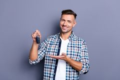 Portrait of his he nice attractive confident cheerful glad bearded guy wearing checked shirt holding in hand remote lock. Portrait of his he nice attractive stock images
