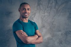 Portrait of his he nice attractive muscular sportive strong powerful cheerful cheery guy wearing trendy blue t-shirt. Folded arms isolated over gray industrial stock photo