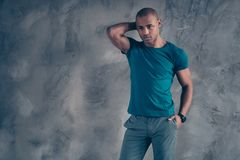 Portrait of his he nice attractive powerful strong guy wearing trendy blue t-shirt modern look touching neck head posing. Isolated over gray industrial concrete stock images