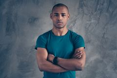 Portrait of his he nice attractive sportive strong powerful guy wearing trendy blue t-shirt modern smart watch clock. Isolated over gray industrial concrete stock photo
