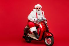 Portrait of his he nice bearded cool cheerful funky Santa hipster riding retro moped December ho-ho-ho North Pole