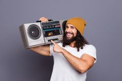 Portrait of his he nice handsome attractive cheerful cheery wavy-haired guy holding in hands pressing button on player royalty free stock photo