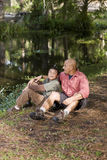Portrait Hispanic father and son outdoors by pond Royalty Free Stock Photos