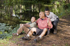 Portrait Hispanic father and sons outdoors by pond Stock Images
