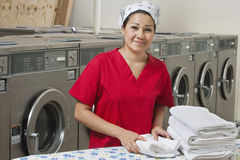 Portrait of a Hispanic female employee with towel in Laundromat Royalty Free Stock Image