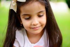 Portrait of hispanic girl in sunny park Stock Photos