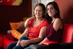Hispanic teenage girl and her grandmother at home. Portrait of a hispanic teenage girl and her grandmother at home attractive beautiful care child couch daughter royalty free stock photos