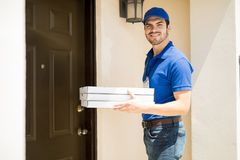 Delivery guy with some pizza. Portrait of a Hispanic young delivery man bringing some pizza to a front door of a house and smiling royalty free stock photos