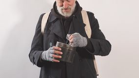 Portrait of homeless beggar with Cup for money, finds large bill in his Cup