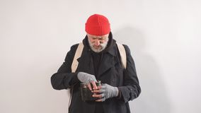 Portrait of homeless beggar with Cup for money, finds paper money in his Cup