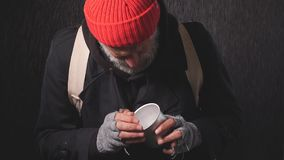 Portrait of homeless beggar in the rain counting change lying in Cup for money
