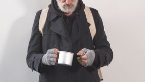 Portrait of a homeless beggar in Studio on white background, pulls bills out of Cup for money