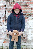 Portrait of a homeless boy with bear. The portrait of a homeless boy with bear Royalty Free Stock Photo