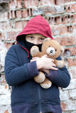 Portrait of a homeless boy with bear. The portrait of a homeless boy with bear Stock Photo