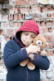 Portrait of a homeless boy with bear Stock Image