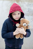 Portrait of a homeless boy with bear Royalty Free Stock Photo