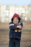 Portrait of a homeless boy with bear Royalty Free Stock Image