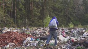Portrait of a homeless man in a dump with a bag on his back. In the bag are empty bottles. Hd stock video footage