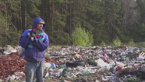 Portrait of a homeless man in a dump with a bag on his back. In the bag are empty bottles. Hd stock footage