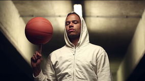 Portrait of a hooded basketball player spinning the ball stock footage