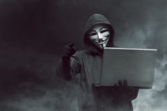 Portrait of hooded hacker with mask holding laptop while standin Stock Image