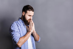 Portrait of hopeful bearded man praying,. Portrait of hopeful bearded man praying. Young guy holding hands clasped near face, looking away, gray studio Stock Photos