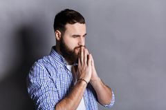 Portrait of hopeful bearded man praying,. Portrait of hopeful bearded man praying. Young guy holding hands clasped near face, looking away, gray studio Stock Image