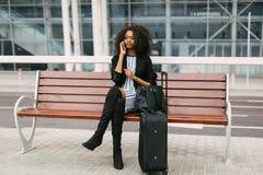 Portrait horizontal de la femme afro-américaine sérieuse s'asseyant sur le banc et parlant par l'intermédiaire du téléphone porta Image stock